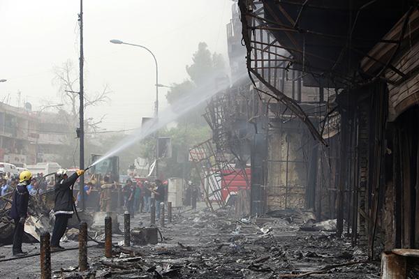 伊拉克首都巴格達的商業區於2016年7月2日晚間,遭到伊斯蘭國的汽車炸彈攻擊,至少造成126人死亡、147人受傷。本圖為消防人員正在爆炸現場滅火。(SABAH ARAR/AFP/Getty Images)