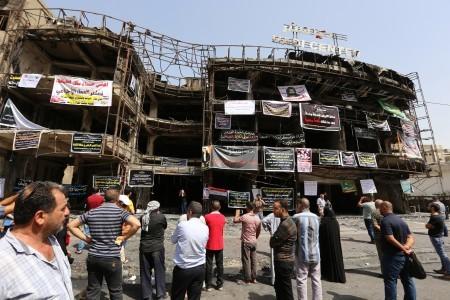 伊拉克首都巴格達上周末發生的自殺爆炸事件死亡人數已升至250人。圖為2016年7月5日,罹難者的親友在發生爆炸的大樓外懸掛了部份罹難者的照片和文字表達哀悼。(SABAH ARAR/AFP)