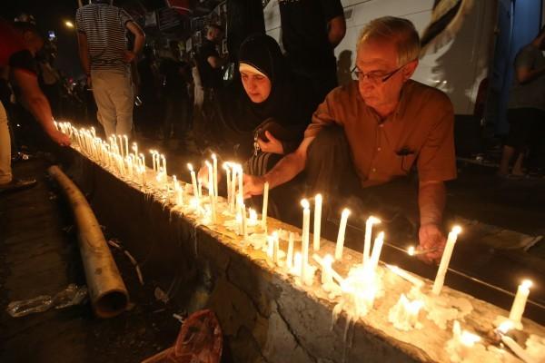 伊拉克首都巴格達上周末發生的自殺爆炸事件死亡人數已升至250人。悲傷的當地居民為罹難者點燃蠟燭哀悼,並祈禱和平。(AFP PHOTO/AHMAD AL-RUBAYE)