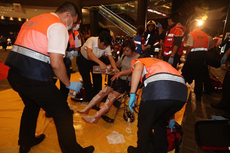 台鐵電聯車7日晚間行駛至松山車站附近時,突然車廂傳出爆炸聲,起火燃燒,乘客尖叫逃出車外,逾十多人受傷,目前還不確定人數,消防人員撲滅火勢並加派救護車到場救人。圖為警消為受傷民眾處理傷勢。(中央社)