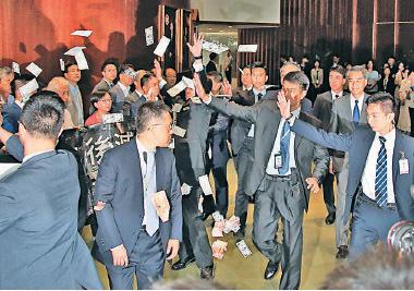 梁振英準備進入立法會議事廳出席答問大會時,遇到泛民議員抗議,有人撒紙錢諷刺他收取UGL五千萬元。(潘在殊/大紀元)