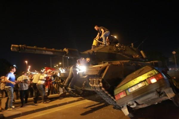 2016年7月16日清晨,在土耳其安塔拉克的一輛坦克碾過一輛汽車,而在附近抗議的人群想要阻止軍方的坦克繼續前進。(ADEM ALTAN/AFP/Getty Images)