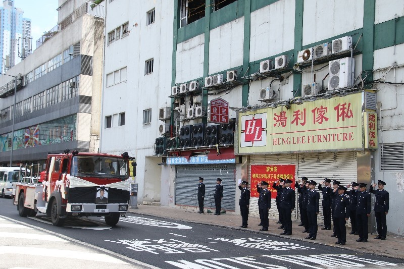 靈車約十時抵達張殉職的火場九龍灣工業村進行路祭。現在消防列隊向靈車敬禮。(Dennis Law/IMAG提供)
