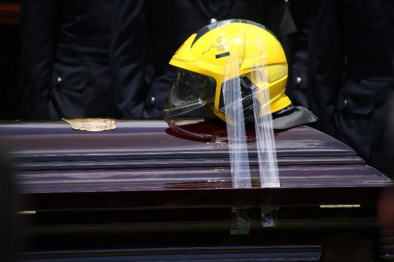 消防以膠帶固定張耀昇生前配戴的消防帽在靈柩上一起下葬。(Dennis Law/IMAG提供)