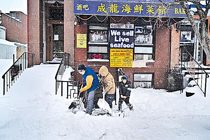 陽光露臉了,美國民眾開始鏟雪。華盛頓中餐館。(AFP)