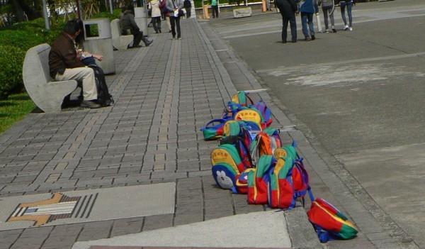 臺北國父紀念館地上,一堆無人看管的小書包。書包的主人們──一群臺北漢家幼稚園的小朋友們,到別處玩耍去了。(曾錚 提供)
