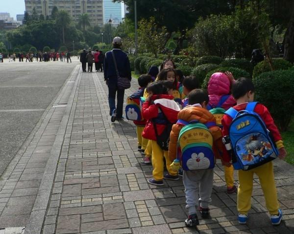 小朋友們遊玩結束後,撿起地上的書包,列隊離開。(曾錚 提供)