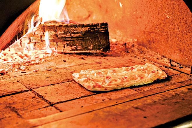 薄皮麵餅加上鮮奶油、黑森林鮮肉和洋蔥,放入燒熱的柴火烤爐。