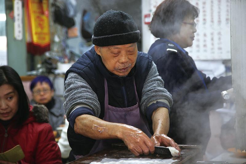 「康記粥店」的陳伯正在拉腸粉。(余鋼/大紀元)