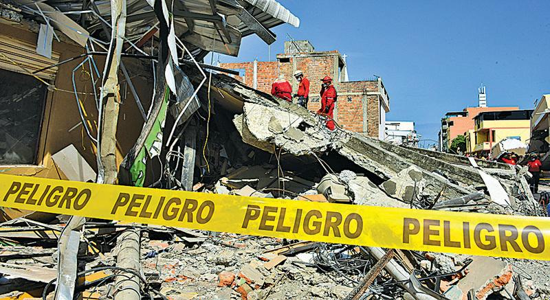 厄瓜多爾配備簡單照明裝備的救援人員,在瓦礫中徒手搜救生還者。(AFP)