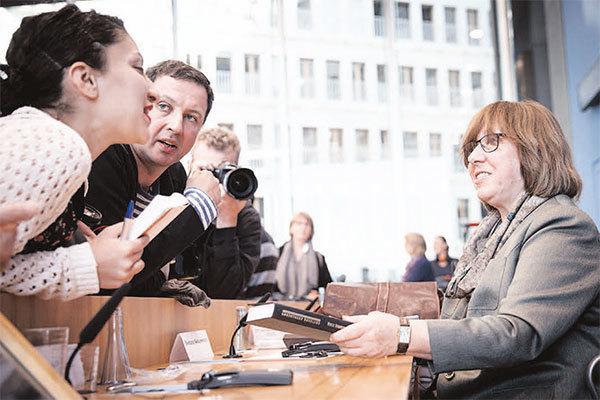 10月10日,得知獲得今年諾貝爾文學獎的消息後,阿列克謝耶維奇在德國柏林參加新聞發布會,與她的書迷親切交談。(Getty Images)