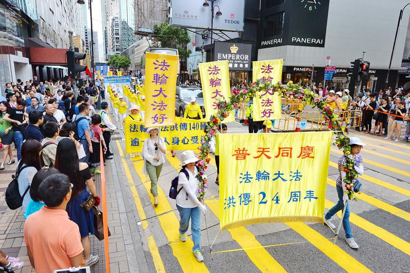 來自各地和香港的部份法輪功學員,在長沙灣舉行恭祝李洪志大師華誕及慶祝世界法輪大法日遊行。圖為遊行經過鬧區吸引許多民眾觀看。(宋祥龍/大紀元)
